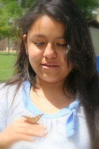 a young girl releasing a live butterfly